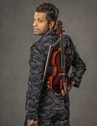 G Pinto - brown suit - with back turned holding violin